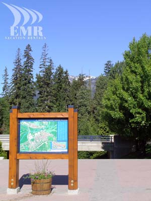 The map at the trail from Blackcomb Village to Whistler village with a view of snow peaked mountians in the back ground.